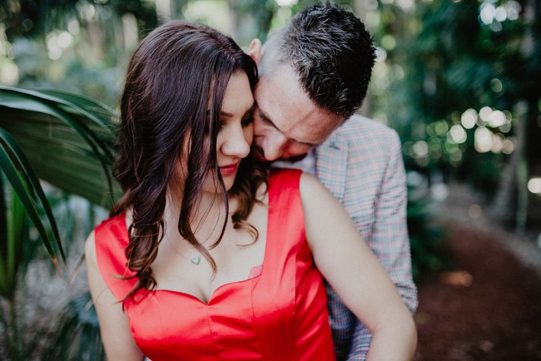man in suit kissed woman in red dress in botanical garden sydney